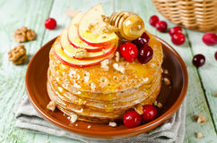 Pancake casalinghi con miele, la mela, i mirtilli rossi ed i dadi Immagini Stock