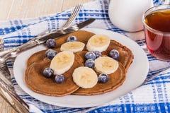 Pancake casalinghi del cioccolato con le bacche e la banana Immagini Stock