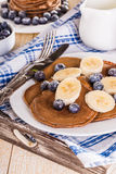 Pancake casalinghi del cioccolato con le bacche e la banana Fotografie Stock