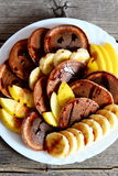 Pancake casalinghi del cioccolato con sciroppo, le banane fresche affettate e le mele su un piatto bianco Fotografia Stock