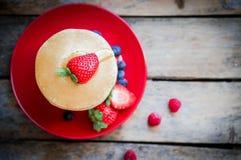 Pancake casalinghi saporiti con le fragole, i mirtilli e l'acero Fotografia Stock Libera da Diritti