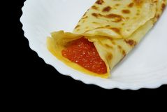 Pancake with caviar. Traditional russian festal day delicacy pancake with caviar isolated on black background Royalty Free Stock Photography