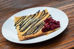 Pancake with a chocolate and cherry. Pancake with a chocolate and cherry on a white plate Stock Images