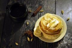 Pancake con burro e miele su un fondo nero Fotografie Stock