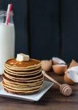 Pancake con burro e miele, una bottiglia di latte, dessert immagini stock libere da diritti