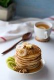 Pancake con i frutti, l'inceppamento ed il cappuccio di tè su una tavola bianca Fotografie Stock Libere da Diritti