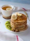 Pancake con i frutti, l'inceppamento ed il cappuccio di tè su una tavola bianca Immagini Stock