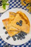 Pancake con i mirtilli, la panna montata e un ramoscello della melissa della menta Fondo blu di legno Primo piano Immagine Stock Libera da Diritti
