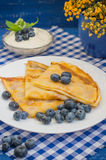 Pancake con i mirtilli, la panna montata e un ramoscello della melissa della menta Fondo blu di legno Primo piano Immagini Stock