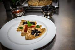 Pancake con il caviale su un piatto bianco Fuoco selettivo shallow fotografia stock