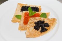 Pancake con il caviale su un piatto bianco Fuoco selettivo shallow fotografia stock libera da diritti