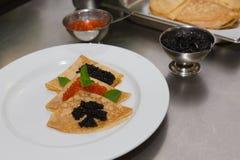 Pancake con il caviale su un piatto bianco Fuoco selettivo shallow fotografie stock libere da diritti