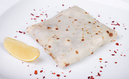 Pancake con il salmone salato su un piatto, limone Fotografia Stock