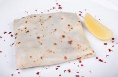 Pancake con il salmone salato su un piatto, limone Immagine Stock