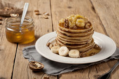Pancake con la banana, i dadi ed il miele Fotografia Stock