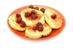 Pancake con la marmellata di amarene sulla zolla rossa fotografie stock