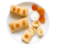 Pancake con la ricotta e le albicocche secche sul piatto bianco isolato su fondo bianco Fotografia Stock Libera da Diritti