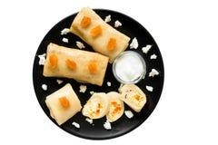 Pancake con la ricotta e le albicocche secche sulla banda nera isolata su fondo bianco Fotografie Stock
