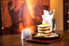 Pancake con la salsiccia e le uova rimescolate in una padella Immagine Stock