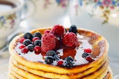 Pancake con le bacche ed il miele rossi e blu Immagini Stock
