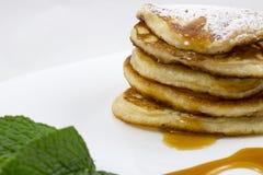 Pancake con le foglie di menta e del miele immagini stock libere da diritti
