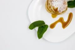 Pancake con le foglie di menta e del miele immagini stock