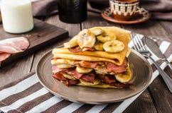 Pancake con lo sciroppo di melassa del bacon, della banana e dell'acero immagini stock