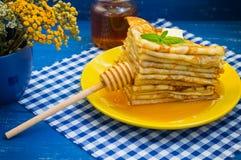 Pancake con miele, burro e un ramoscello della melissa della menta Fondo blu di legno Primo piano Immagini Stock Libere da Diritti