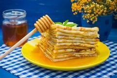Pancake con miele, burro e un ramoscello della melissa della menta Fondo blu di legno Primo piano Fotografie Stock