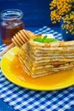 Pancake con miele, burro e un ramoscello della melissa della menta Fondo blu di legno Primo piano Fotografie Stock Libere da Diritti