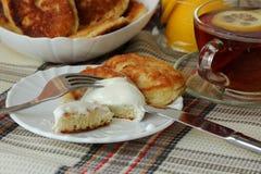 Pancake con panna acida e una tazza di tè per la prima colazione Fotografie Stock