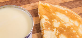 Pancake and condensed milk. On a wooden background, very tasty stock images