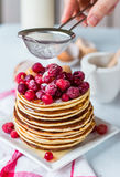 Pancake with cranberries, raspberries and powdered sugar, hands Stock Photos