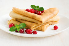 Pancake with cranberry and mint. Close-up on wooden table Stock Image