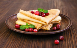 Pancake with cranberry and mint. Close-up on wooden table Royalty Free Stock Photo