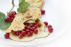 Pancake or crepe with red currants on a white plate Royalty Free Stock Photos