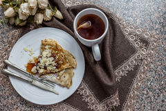 Pancake with cup of tea on table cloth Stock Photo