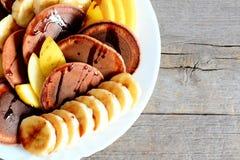Pancake del cacao con frutta fresca Pancake al forno del cacao con sciroppo, le banane affettate e le mele su un piatto bianco Immagine Stock