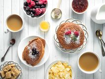 Pancake del cioccolato della prima colazione con le bacche, una tazza di caffè con crema, un miele ed i cereali Vista superiore Immagine Stock