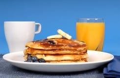 Pancake del mirtillo con spremuta Fotografia Stock