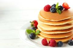 Pancake deliziosi con le bacche su fondo di legno bianco Fotografia Stock Libera da Diritti