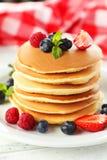 Pancake deliziosi con le bacche su un fondo di legno bianco Fotografia Stock Libera da Diritti
