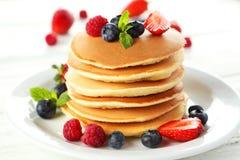 Pancake deliziosi con le bacche su un fondo di legno bianco Fotografie Stock Libere da Diritti