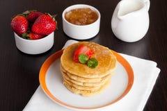 Pancake deliziosi con le fragole fresche su un piatto, su un inceppamento e su una m. Fotografia Stock Libera da Diritti