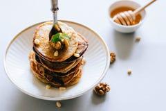 Pancake della banana con le noci ed i dadi di cedro Fotografia Stock