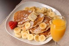 Pancake della banana con spremuta Fotografie Stock