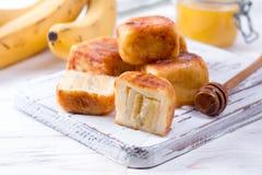 Pancake della ricotta sotto forma di cubi con miele su un fondo bianco immagine stock