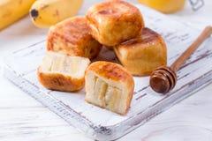 Pancake della ricotta sotto forma di cubi con miele su un fondo bianco fotografia stock libera da diritti