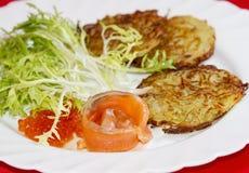 Pancake di patata con un pezzo di caviale di color salmone e rosso Immagine Stock