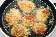 Pancake di patata - Latkes che friggono in olio Immagine Stock